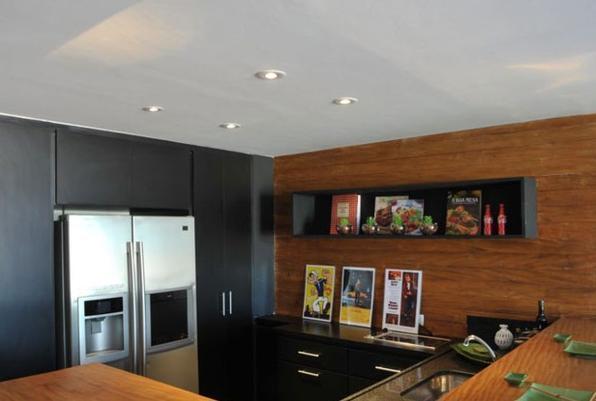 Armário pintado de preto compõe cozinha moderna com bancada de madeira