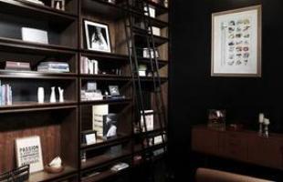 A decoração da sala mistura o preto com marrom e móveis em madeira
