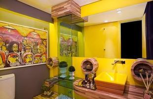 O lavabo super colorido conta com bancada, cuba e acabamentos feitos de madeira de demolição. A cor amarela dá mais alegria ao ambiente