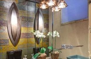 Bancada em madeira, cuba de pedra e luminária em tela de arame compõem a decoração do banheiro. Na parede e no piso, a composição é de pedra ardósia. Dica: espelho amplia o ambiente