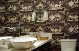 Um tecido estampado nas paredes de um lavabo pequeno: o espelho cai como uma luva no local, dando sensação de amplitude para todos os lados, no projeto assinado pela arquiteta Renée Sbrana