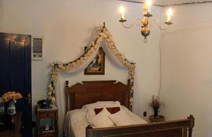 Flores e objetos religiosos e peças de antiquário são a base da decoração do quarto do casal. O destaque do espaço fica por conta do dossel que emoldura a cama de madeira maciça