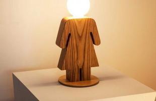 Luminária Menina de mesa em madeira de reflorestamento com cabeça em vidro.