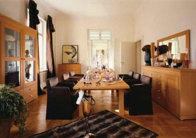 Sala de jantar com móveis de madeira clara e elementos de decoração em tons escuros - Divulgação hülsta
