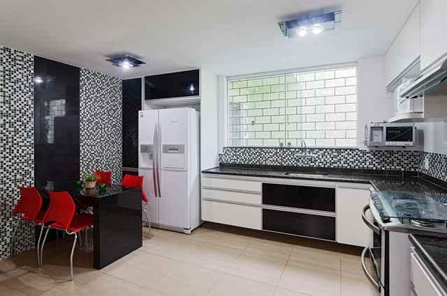 O preto traz pureza e aconchego, deixando a cozinha sofisticada, enquanto o vermelho aquece e traz energia, harmonizando o ambiente - Divulgação/Laura Santos