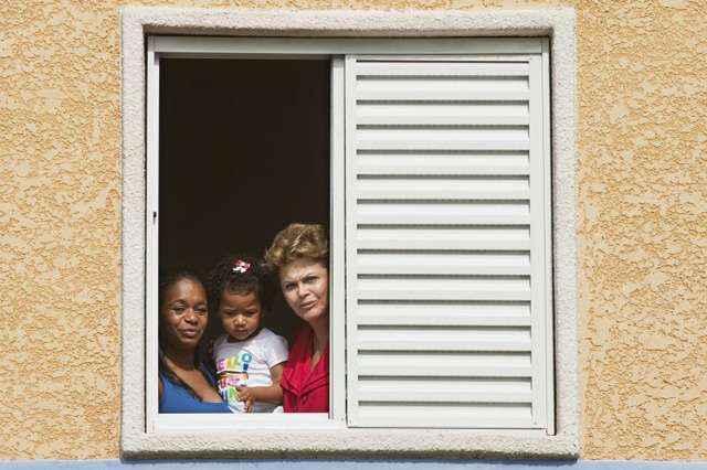 No detalhe da janela, Dilma aparece junto a uma das famílias contempladas durante cerimônia de entrega das chaves, na Bahia, em 2013 - Nelson Almeida/AFP