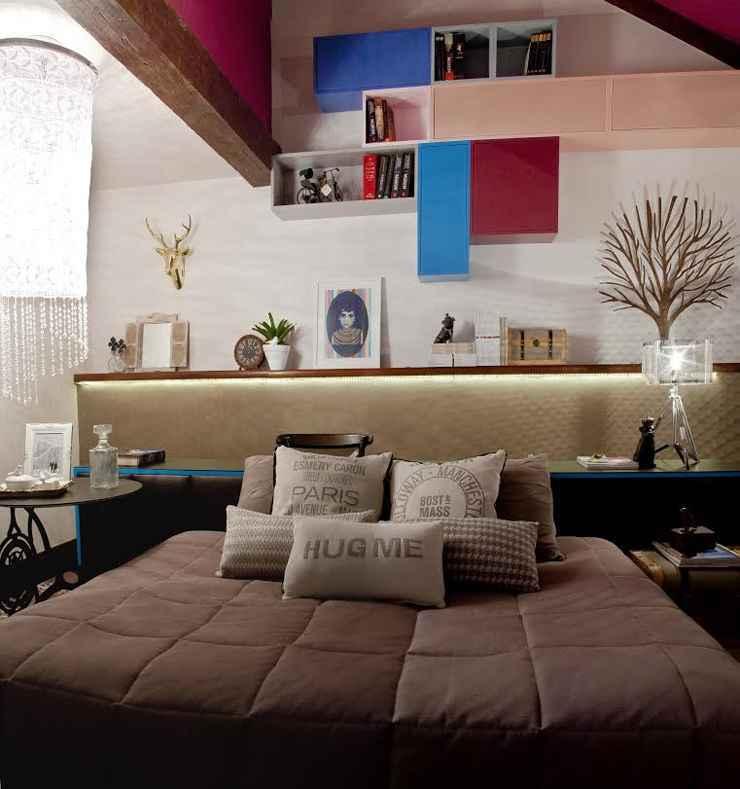 Neste projeto da designer Analu Guimarães, a cama encostada lateralmente atrás do móvel e as inúmeras almofadas dão a cama a impressão de sofá. - Divulgação