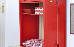 Divertido e colorido, o móvel vermelho com ajuda da almofada listrada, se transformou em uma caminha para o cachorro