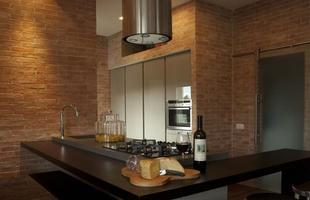 Tijolos na parede e móveis pretos remetem a uma decoração rústica e bastante charmosa