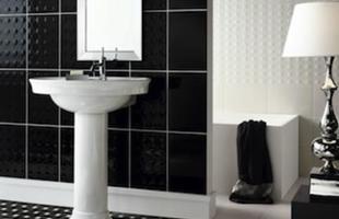 A decoração do banheiro conta com azulejos e pastilhas pretas e brancas