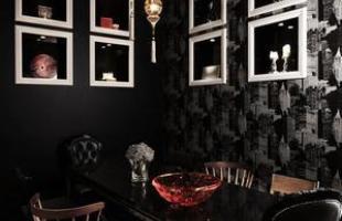 Nesta sala de jantar, ao contrário da maioria dos ambientes, as paredes e o chão são pretos e os elementos de decoração são na cor branca