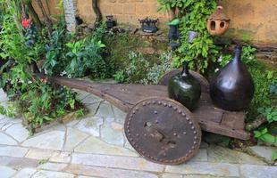 No jardim, o carro de boi serve de apoio para vasos e realça a atmosfera rústica do ambiente