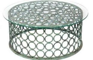 Mesa produzida em metal e tampo de vidro, com acabamento desgastado pelo tempo e argolas vazadas que garantem maior valor estético ao produto.