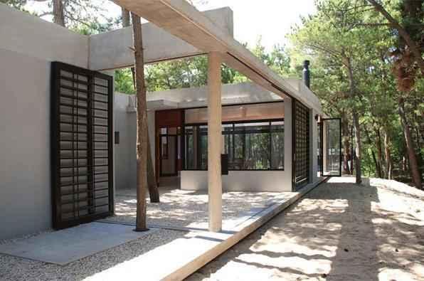 Projeto arrojado esbanja técnica em arquitetura que alia janelas de vidro e fachada com cobertura de concreto aparente em casa construída dentro de um bosque na Argentina