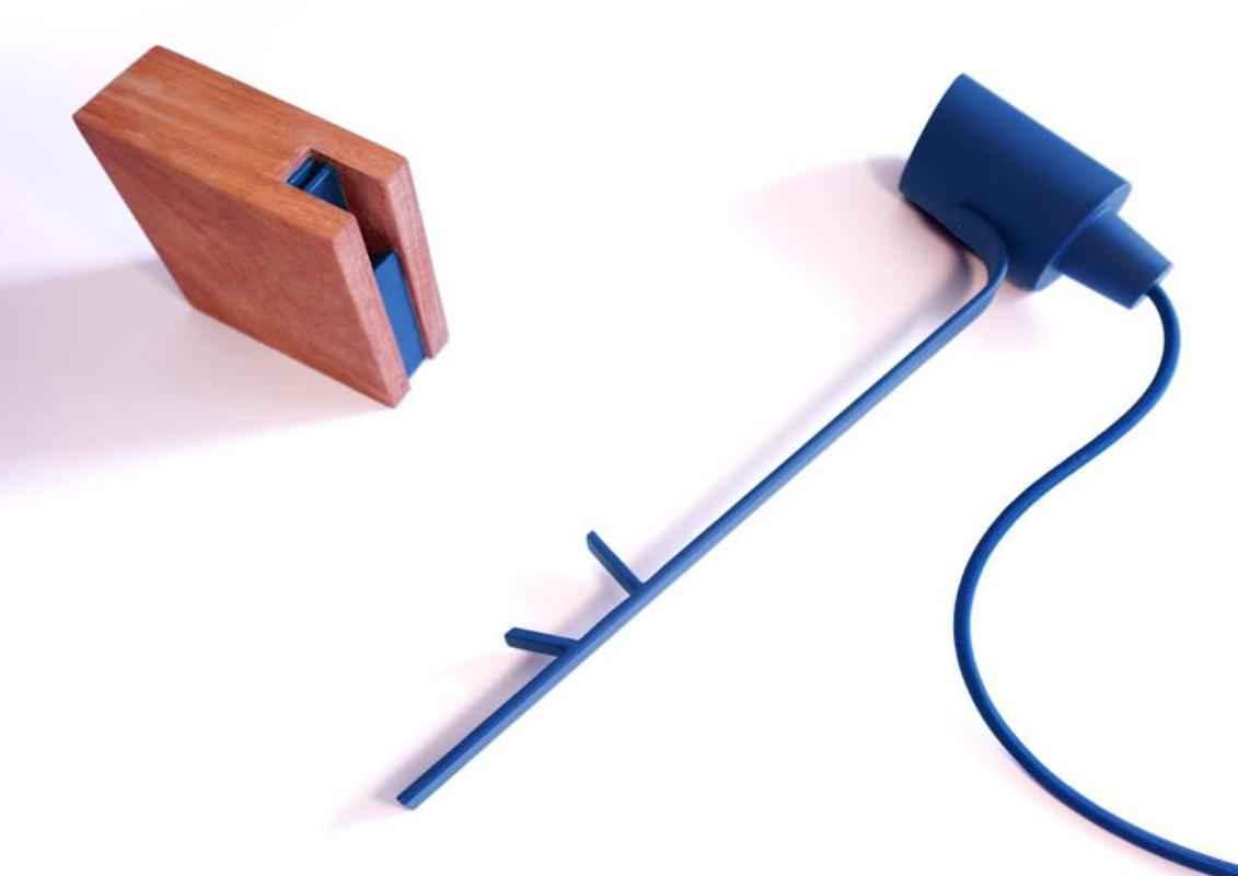 Esta luminária de mesa é marcada pela simplicidade de seu design e pela flexibilidade no posicionamento do foco de luz, graças a um cubo de madeira que funciona como apoio e a uma barra metálica. Assim, o foco de luz pode ser ajustado de diversas formas sobre esse apoio. A ideia por trás deste funcionamento é facilitar o manuseio da peça, sem que sejam necessários complexos sistemas de ferragens. A consciência ambiental também marca a peça: a madeira da base é sempre reaproveitada do processo artesanal da produção da fábrica. E esta madeira é tipicamente brasileira: são utilizadas espécies somente vindas de nossas florestas. Seus diferentes tons proporcionam combinações diversas com a haste, que tem as cores básicas e uma opção corten