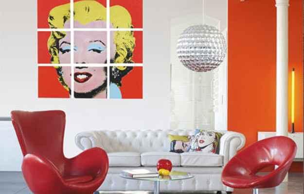Uma das principais obras de Andy Warhol, que retrata a atriz Marilyn Monroe, as almofadas e os móveis coloridos decoram a sala com o estilo Pop Art - Reprodução/Internet