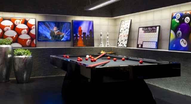Nesta sala de jogos a televisão se misturou com a decoração, que é composta por quadros coloridos - Reprodução/Internet