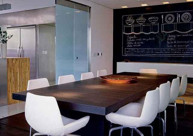 Na sala de jantar, a parede do fundo recebeu pintura com tinta lousa. Assim, a família pode anotar recados e lembretes - Reprodução/Internet