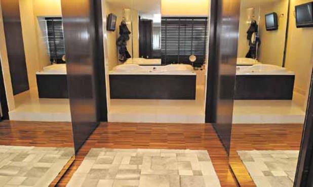 Com imensas portas de madeira, o closet reveza a atenção com uma banheira  -