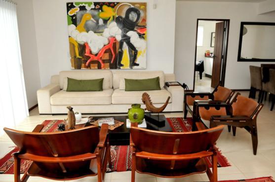 Uma das salas da casa compartilha a paixão pelas artes plásticas e as cadeiras de Sérgio Rodrigues -