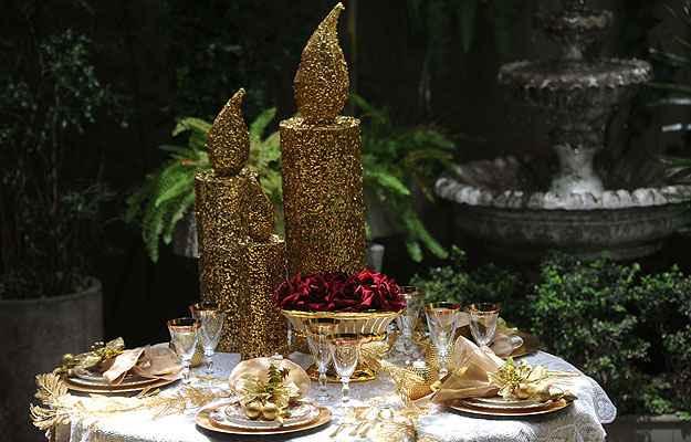 Adornos centrais compostos com uma grande escada, taças vermelhas e pratos dourados em uma composição que se transforma em mosaico brilhante - Leandro Couri/EM/D.A Press