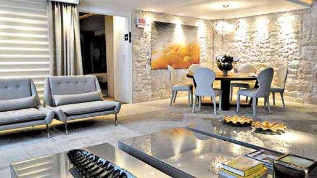 Na sala feita pelo arquiteto Robson Nascimento para um evento de decoração, o jogo de luz na parede de pedra torna o ambiente mais elegante -