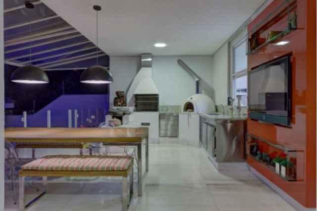 Ambiente gourmet criado pela decoradora Maria Cristina Bahia, o nicho transparente faz as vezes de aparador e não briga com a parede vermelha  - Juliana Buli/Divulgação
