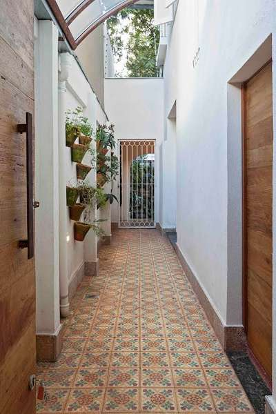 Para este corredor de área externa, a arquiteta Marina Dubal apostou em piso de ladrilho hidráulico e em plantas para a parede - Henrique Queiroga)