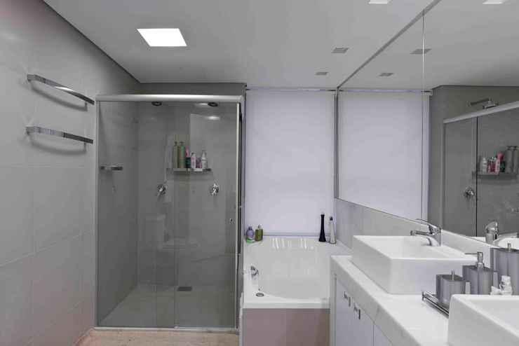%u200BProjeto Iara Santos: A cortina foi inserida na parede da banheira, ao lado do espelho. A solução ficou muito discreta e resolveu o problema de uma janela inconveniente. - Divulgação
