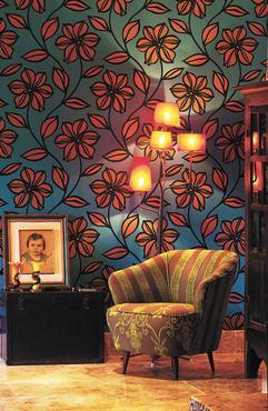 Poltrona de pé palito, com forro que se destaca pela mistura de estampas, papel de parede colorido e um retrato antigo valorizam o ambiente hipster  - Daniel Mansur/Divulgação