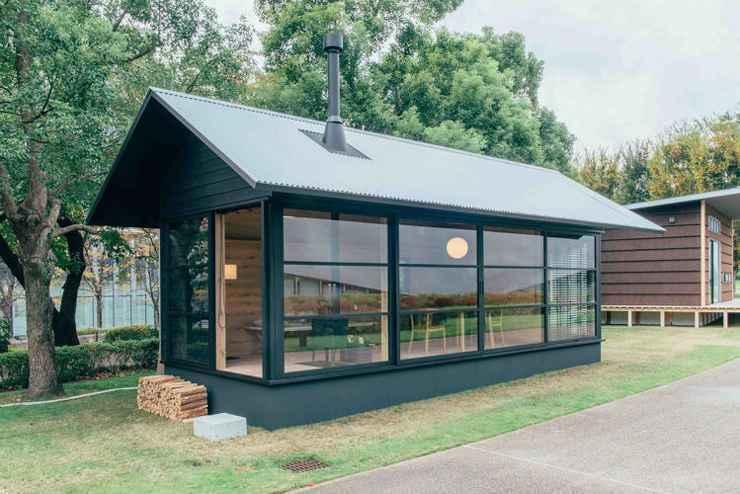 Naoto Fukasawa optou por uma cabana com parede de vidro emoldurada por uma madeira rústica no interior e preta no exterior, além de um fogão de ferro fundido. - Divulgação